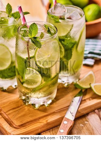 Alcohol drink. On wooden boards three glasses with alcohol drink and ice cubes. A drink number forty six cocktail mohito with knife and mint leaf. Country life. Light background.