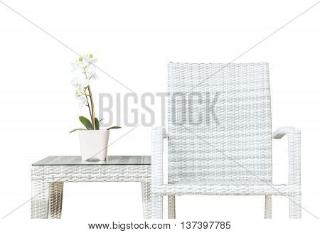 Closeup artificial plant with white orchid flower on pink flower pot on wood weave table with wood weave chair isolated on white background beautiful interior in relaxation concept