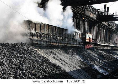 Delivering quenched coal to stocking area on heavy industrial plant.