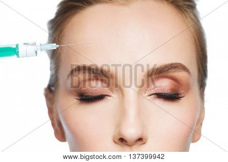 people, cosmetology, plastic surgery, anti-aging and beauty concept - beautiful young woman face and syringe making lifting injection to forehead over white background