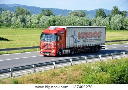 Dolny Hricov, Slovakia - June 29, 2016: Red moving Mercedes-Benz Actros truck coupled with semi-trailer located on slovak D1 highway surrounded by green field and trees.