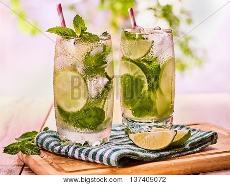 Alcohol drink. On wooden boards two glasses with alcohol drink and ice cubes. A drink number forty seven cocktail mohito with knife and mint leaf. Country life. Light background.