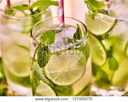 Alcohol drink. On wooden boards part of three glasses with alcohol cocktail drink and ice cubes. Drink number forty four cocktail mohito and cube ice with straw. Country life. Light background.