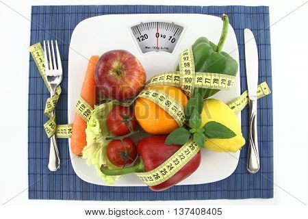 Fruits and vegetables with measuring tape on a plate as weight scale