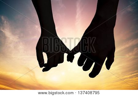 Silhouette of touching hands in sunset. Love concept.