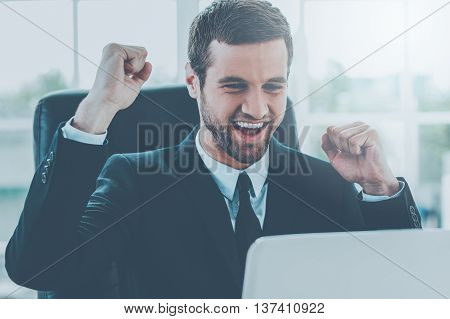 Celebrating success. Happy young man in formalwear looking at computer monitor and gesturing while sitting at his working place
