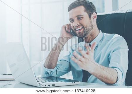 Great news! Happy young man in formalwear looking at computer monitor and talking on the mobile phone while sitting at his working place