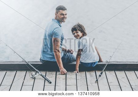 Nice day for fishing. Rear view of father and son sitting at the quayside and looking over shoulder while fishing rods laying near them