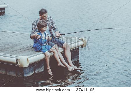 Casting that fish off. Top view of father and son fishing together on quayside