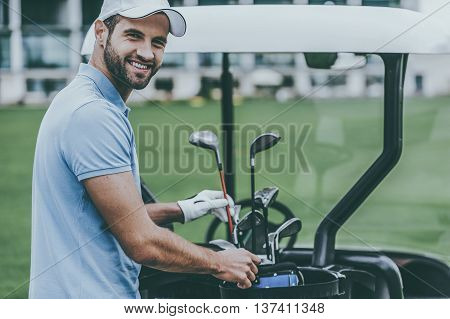 Choosing the driver. Handsome young male golfer choosing driver while standing near the golf cart