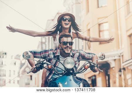 Scooter ride. Beautiful young couple riding scooter together while happy woman keeping arms outstretched and smiling