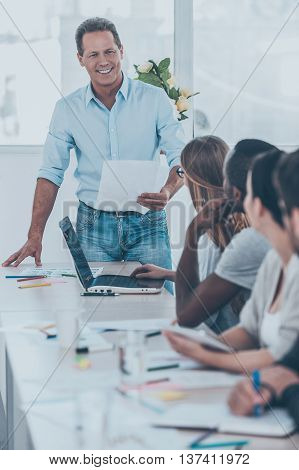 Announcing good news. Group of business people sitting in a row at the table while mature man holding paper and smiling