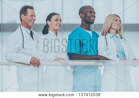 Confident medical experts. Low angle view of four confident doctors standing close to each other and looking away while leaning at the handrail