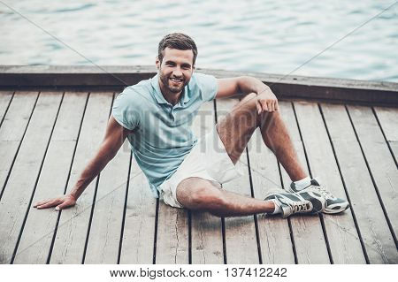 Sporty young man. Handsome young man smiling and looking at camera while relaxing on quayside