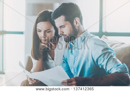 Some paperwork. Concentrated young man holding documents and looking at them while woman sitting close to him and holding hand on chin