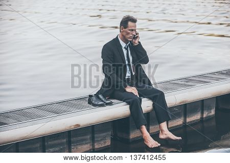Bad news. Depressed mature businessman talking on the mobile while sitting barefoot at the quayside