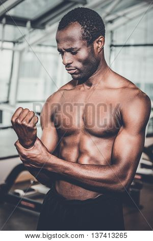 Feeling pain in hand. Frustrated African man touching his arm and expressing negativity while standing in gym