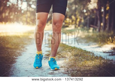 athlete running through the woods. Feet, bottom view