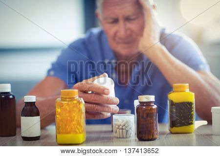 Senior man suffering from headache with prescription bottle at home