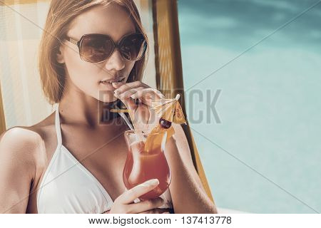 Enjoying summer. Beautiful young woman in white bikini drinking cocktail while relaxing in deck chair near the pool