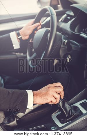 Driving his new car. Close-up of man in formalwear driving car