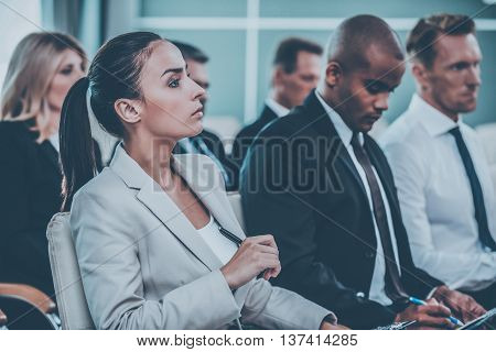 Interesting facts. Group of business people in formalwear sitting at the chairs in conference hall and writing something in their note pads