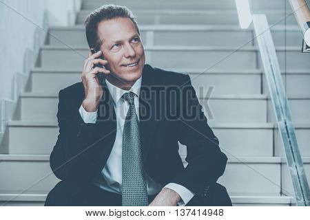 Always in touch. Cheerful mature man in formalwear talking on the mobile phone and smiling while sitting on staircase