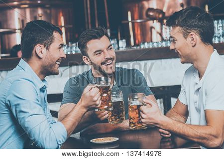 Great time in bar. Three cheerful friends drinking beer and chatting in bar
