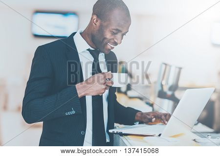 Inspired with fresh coffee. Cheerful young African man in formalwear using his laptop while standing at the bar