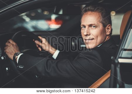 Side view of cheerful senior man in formalwear sitting in car and looking over shoulder