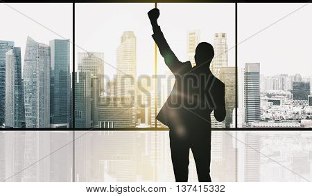 business, success, gesture and people concept - silhouette of happy businessman raising fist and celebrating victory over office window and singapore city skyscrapers background and sun light