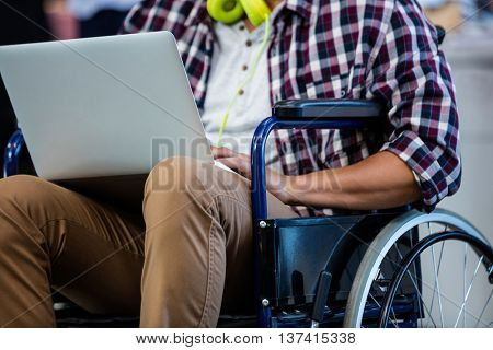 Designer in a wheelchair with a computer in the office