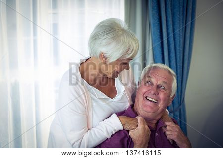 Senior couple looking at each other and smiling in living room