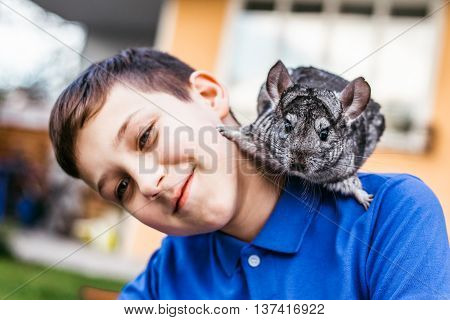 cheerful boy plays with his chinchilla in the courtyard of the house in spring