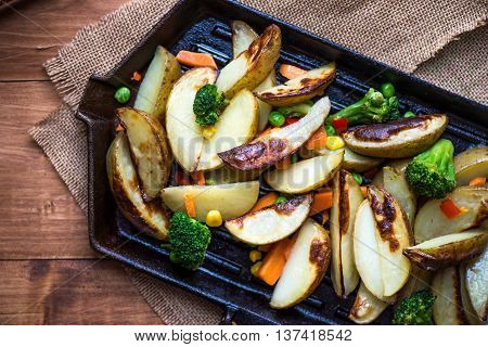 Potato Wedges With Vegetables On Iron Cast Pan