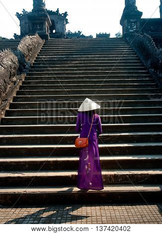 Hue, Vietnam, March 25, 2016 Hue young woman, dressed in traditional dress, walk, ruins ancient capital, Hue City, Vietnam