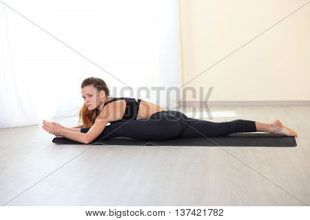 Young Woman Stretching Legs in Splits Position on yoga mat in bright room. Working on Flexbility and stretch the muscles.