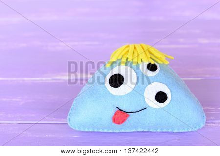 Funny blue felt monster toy isolated on a lilac background. Soft stuffed children alien toy. Simple Halloween crafts for kids
