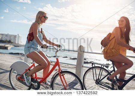Best Friends Cycling Along Seaside Promenade