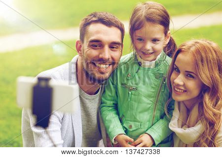 family, childhood, technology and people concept - happy father, mother and little daughter taking picture by smartphone selfie stick in park
