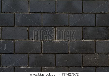 Background of black tiles on a house facade cladded in the pattern of bricks