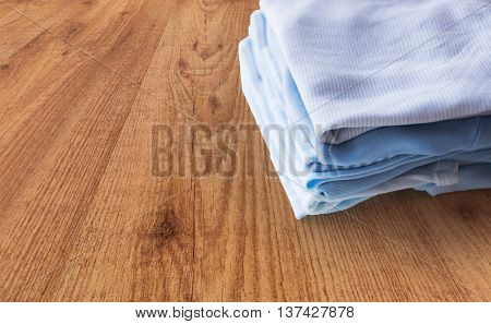 clothing, babyhood, motherhood and object concept - close up of pile of baby clothes for newborn boy folded on wooden table