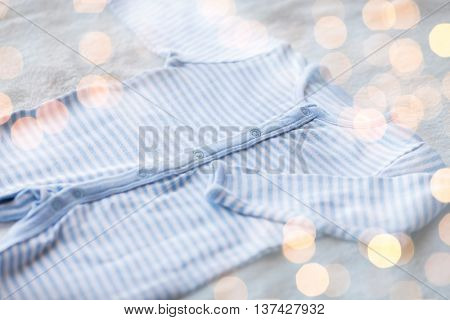 baby clothes, babyhood, motherhood and object concept - close up of blue bodysuit on towel for newborn boy with holidays lights
