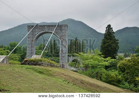 Majestic cable stony bridge for pedestrians spanning over the green valley in Nikko, Japan