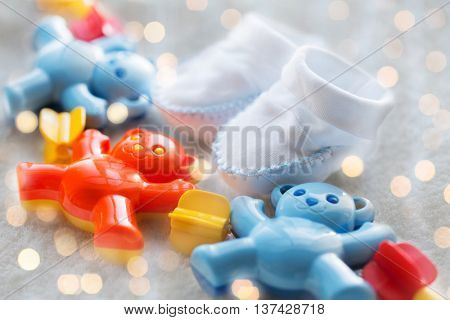 babyhood, childhood, toys, clothing and object concept - close up of baby rattle and bootees for newborn boy on towel with holidays lights