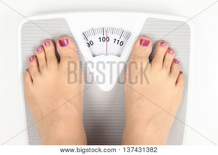 Woman' s feet on bathroom scale isolated in white