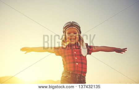 happy child dreams of traveling and playing in aviator pilot opened arms outdoors in summer