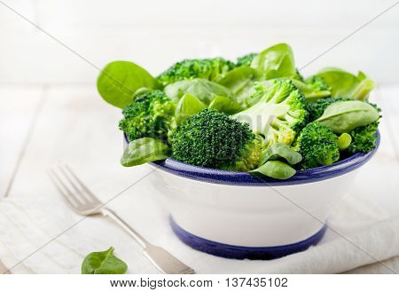 Broccoli, baby spinach and green beans salad in ceramic bowl with olive oil on a white wooden background.