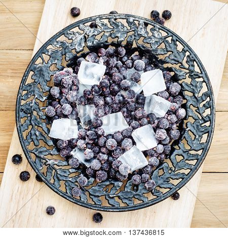 Top view of frozen black currant with pieces of ice on a black vintage plate