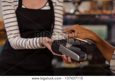 Hand of customer paying by bank card reader with his smartphone in the bar